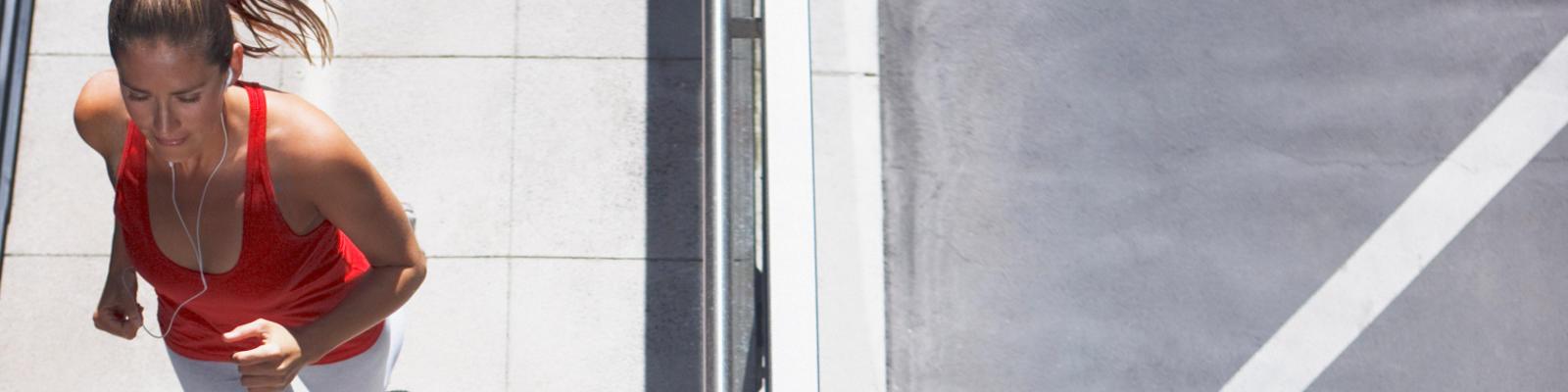 An overhead view of a woman running on a sidewalk