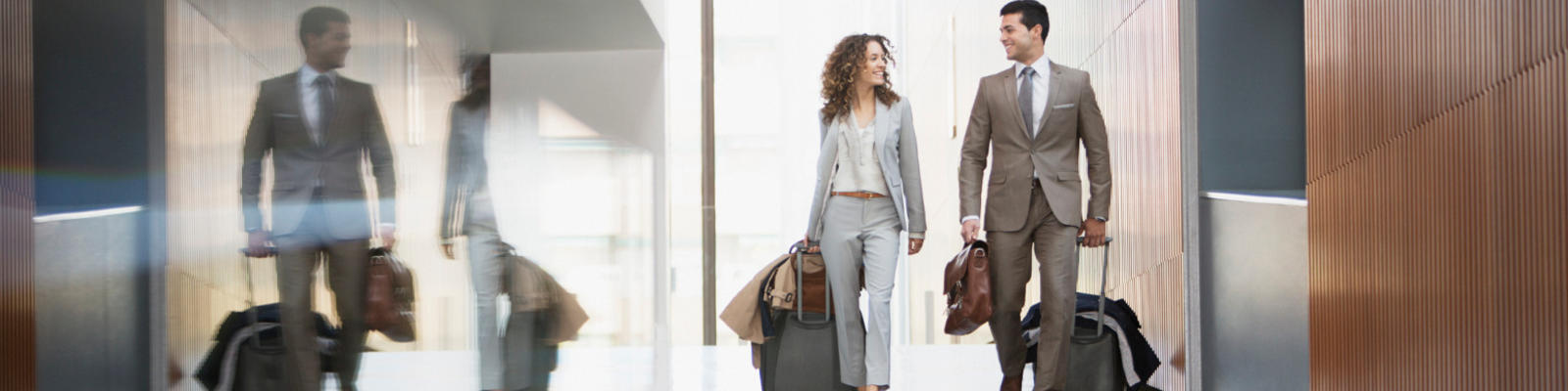 Two co-workers walking together through an airport with their carry-ons in tow