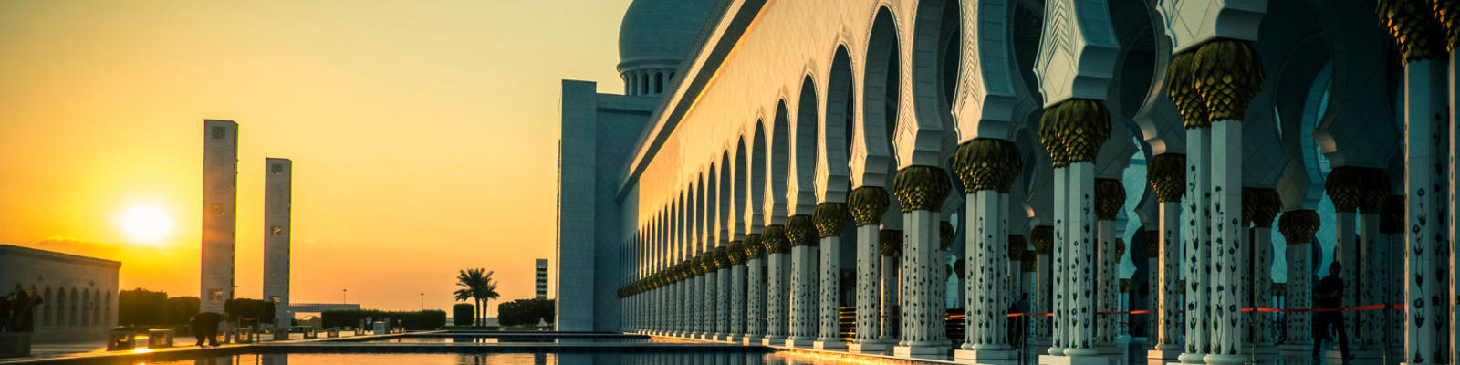 An external view over a reflection pool at sunset at the Grand Mosque in Abu Dhabi