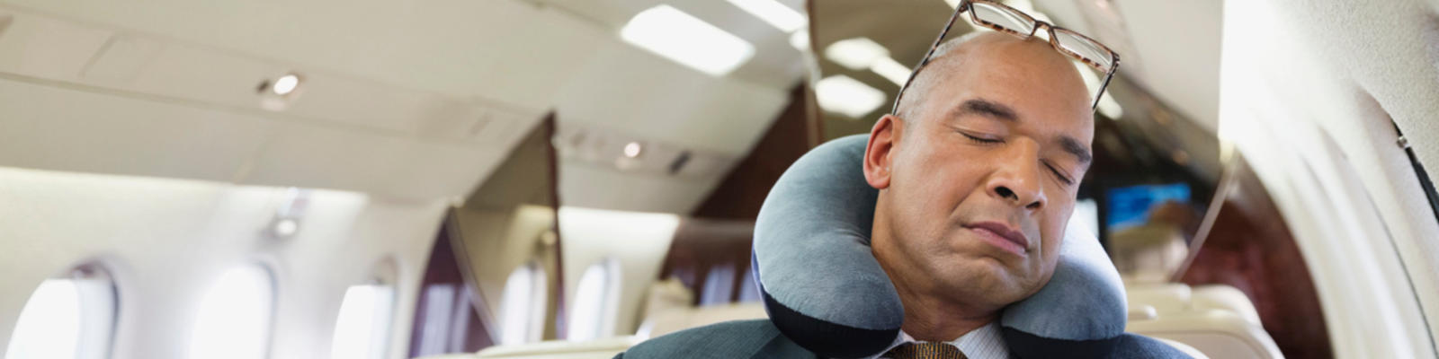 A man sleeping on a plane with a neck pillow around his neck