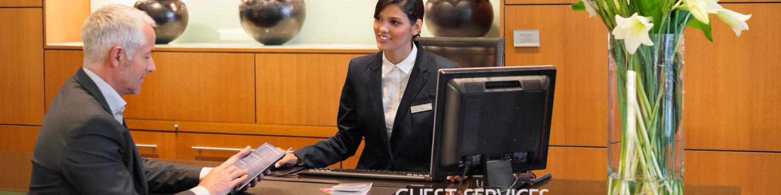 A professional man getting assistance at the hotel Guest Services desk
