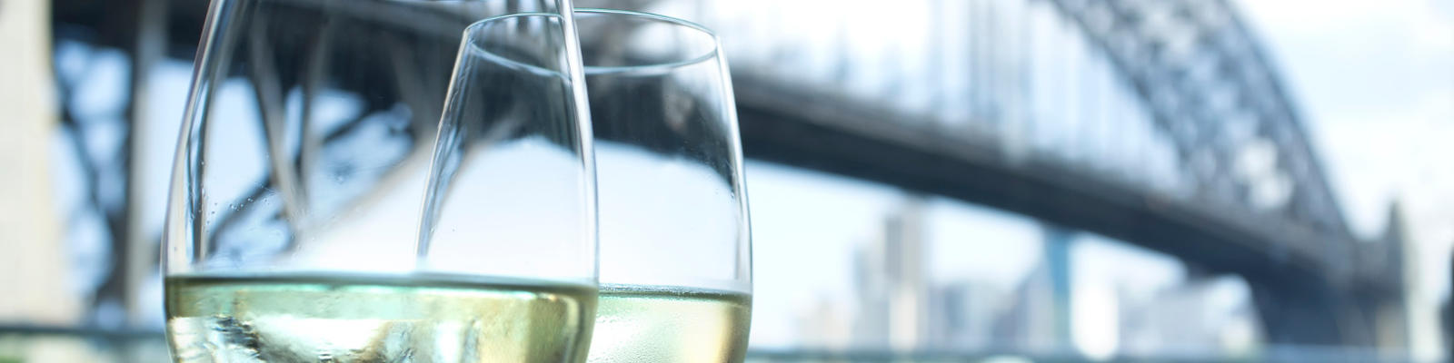 Close up of two glasses of wine with Sydney Harbour Bridge in the background