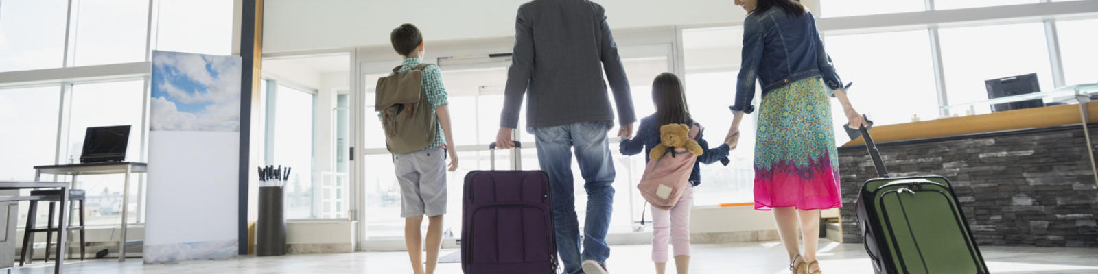 A family of four walking through the airport hand in hand with their bags.