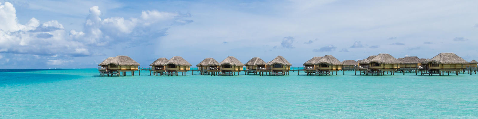 A distant shot of luxury overwater bungalows over the blue waters of Bora Bora
