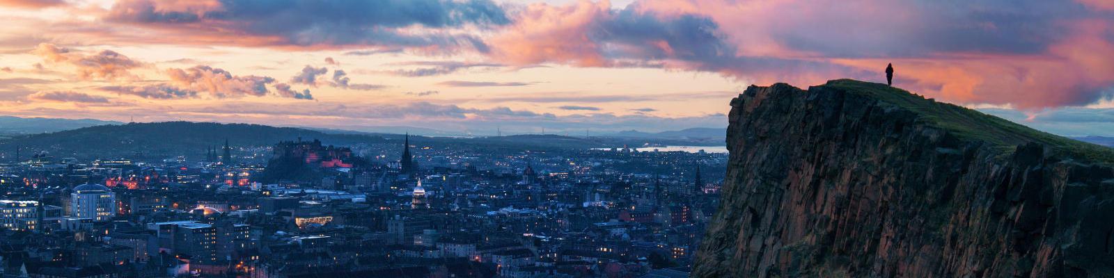 man on mountain over edinburgh sunset
