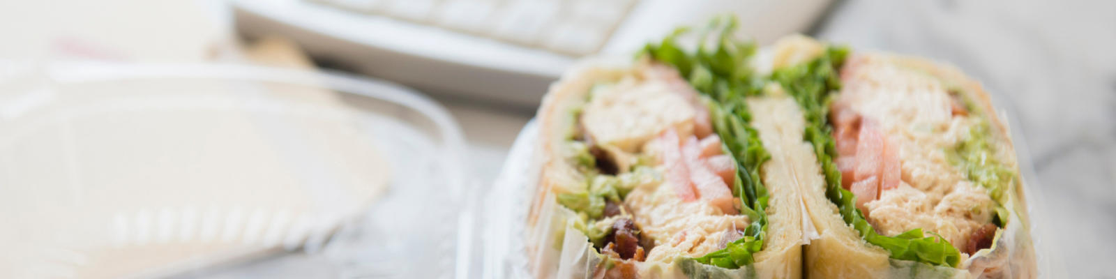 A sandwich wrap sitting on an office desk with a keyboard in the background