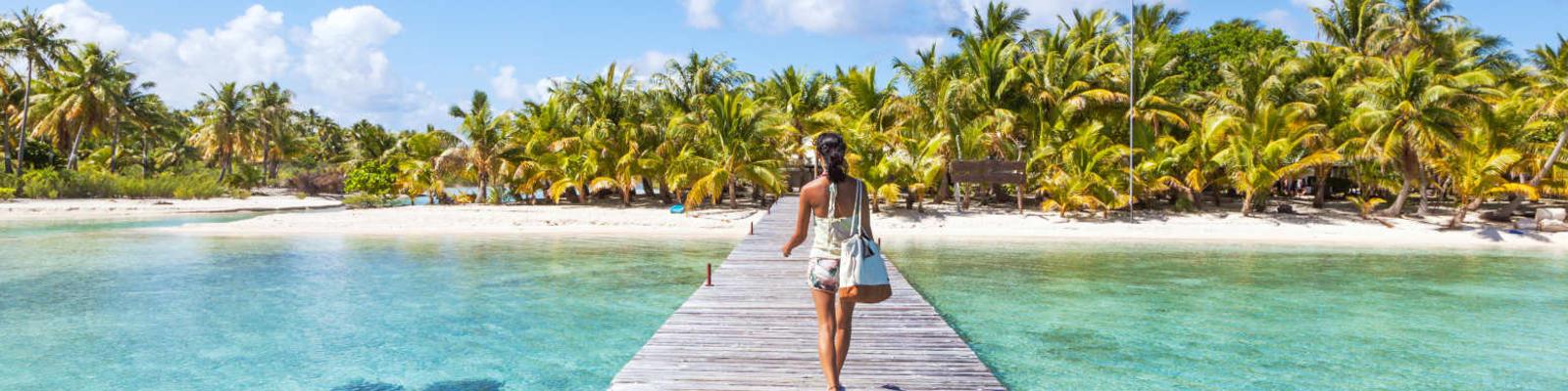 woman walking on boardwalk to tropical island