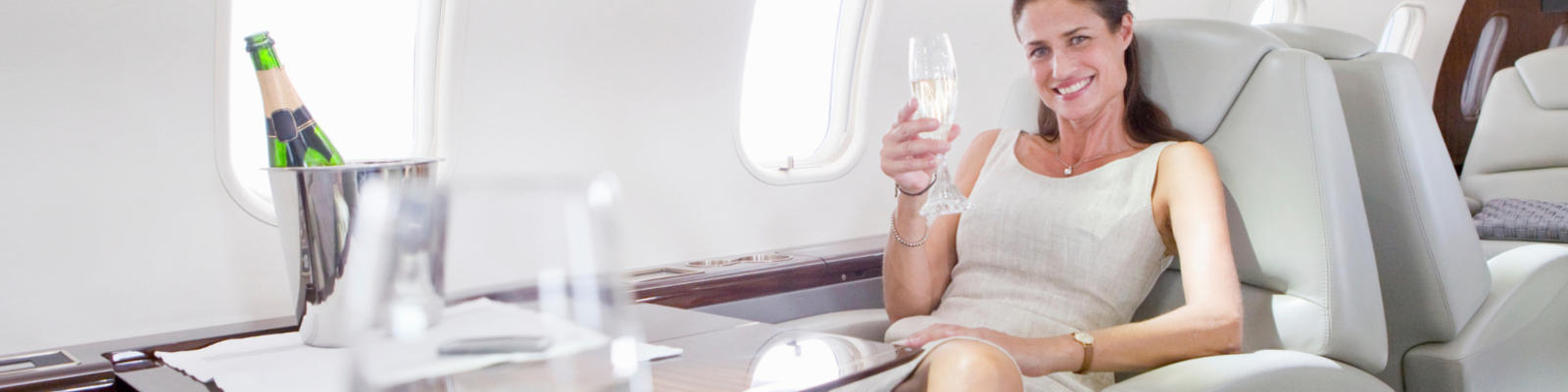 A woman holding a glass of champagne in fancy airplane seat.