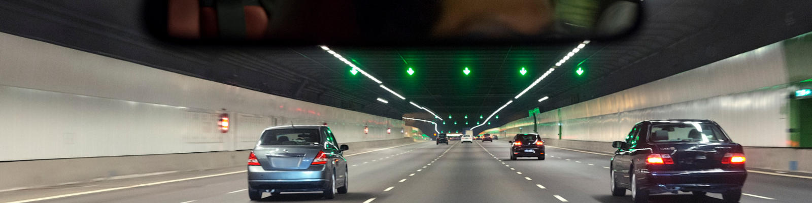A view of cars driving through a tunnel from the point of view of a driver of the car at the rear