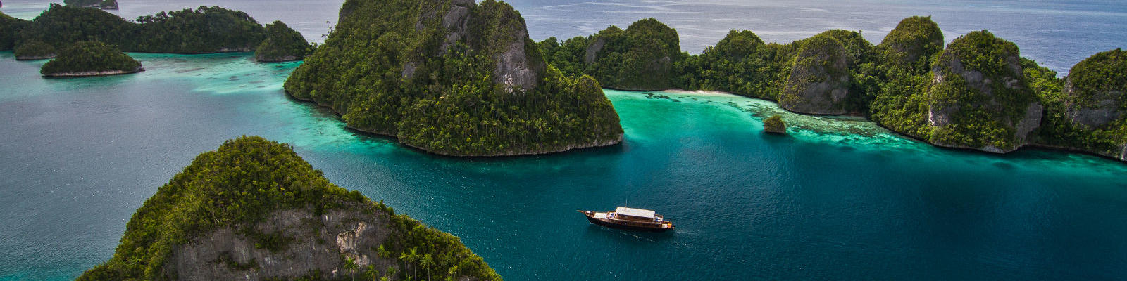 sailing boat in papua new guinea waters with islands