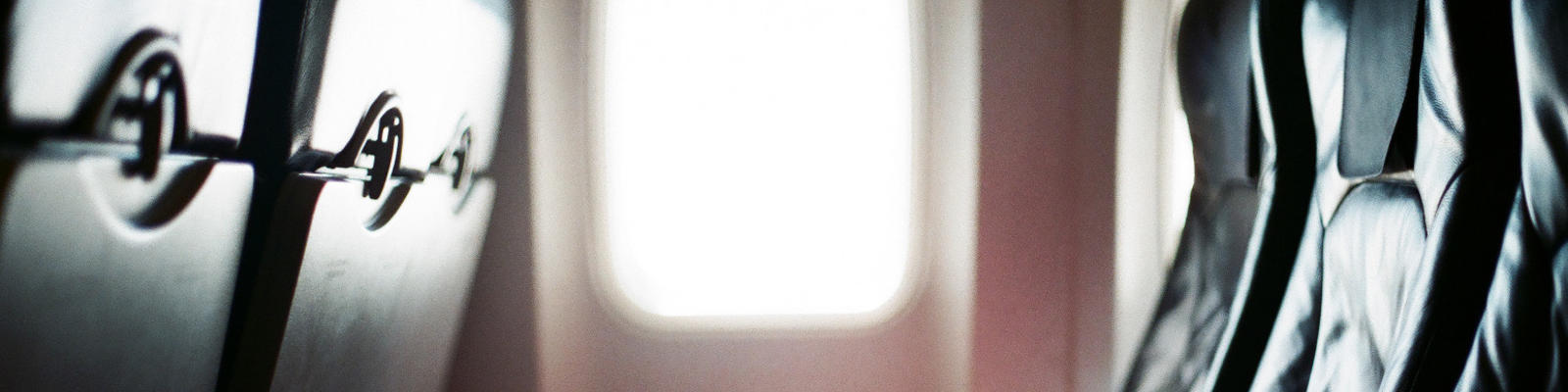 A row of seats on an airplane with sunlight coming in from the window