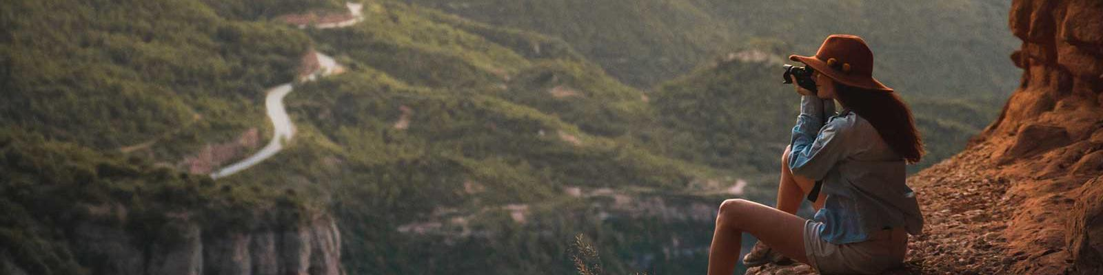 girl on mountain taking photo