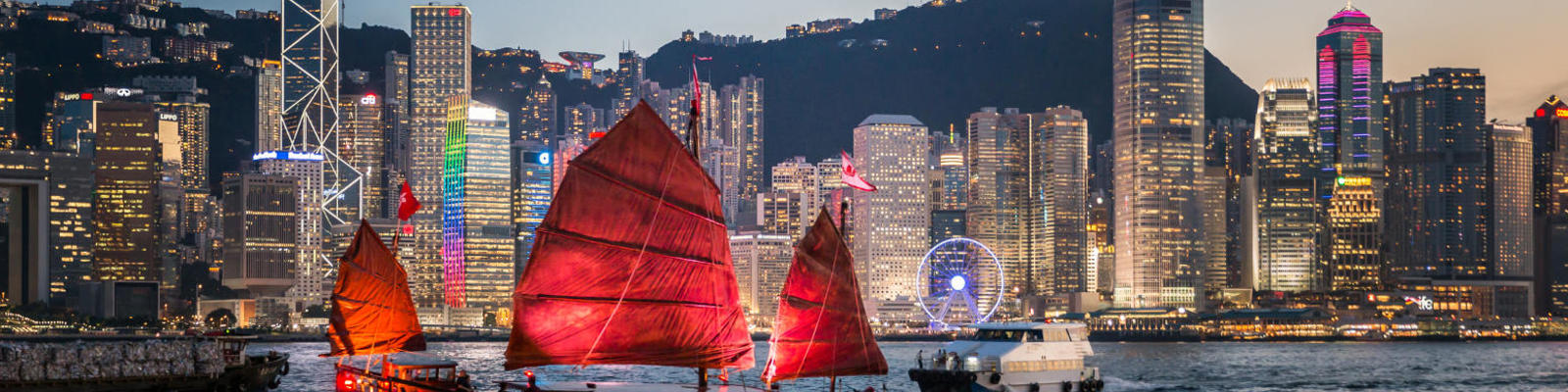 A junk boat sailing in front of the Hong Kong skyline at night