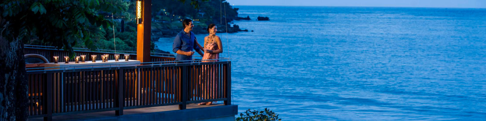 Two people standing on a balcony with drinks overlooking the ocean
