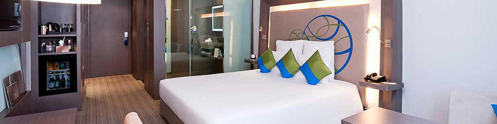 An internal view of a hotel room looking over the bed to the door