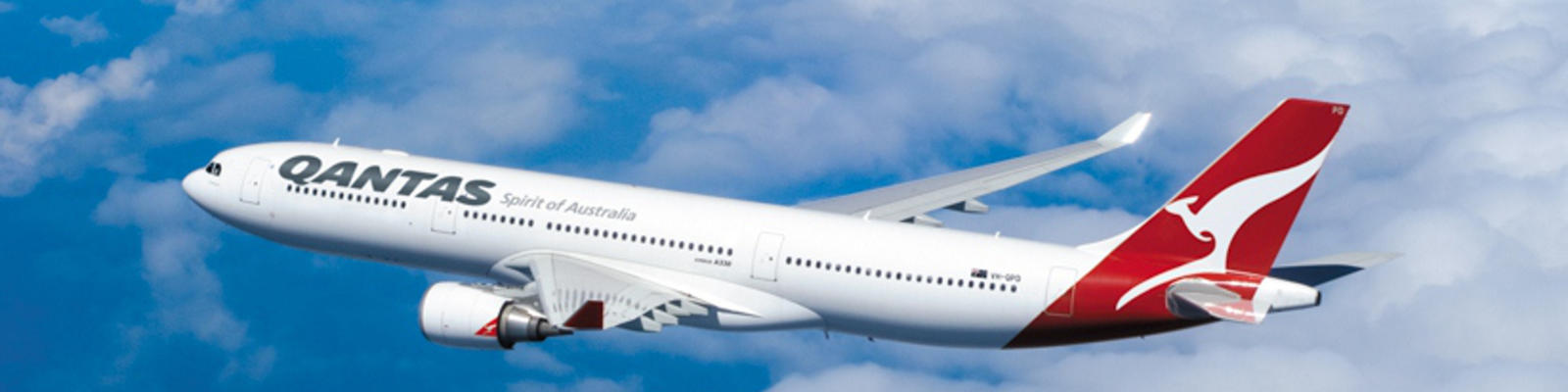 A Qantas A330 flying through the blue skies with fluffy white clouds in the background
