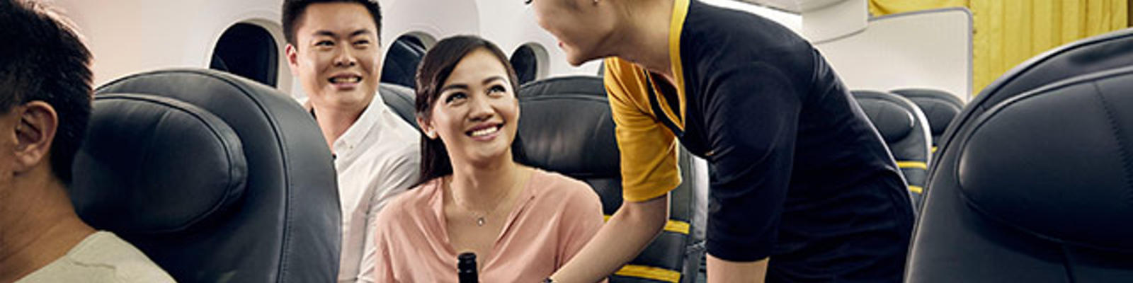 A man and a woman sitting in business class on Scoot, being served some food and drinks