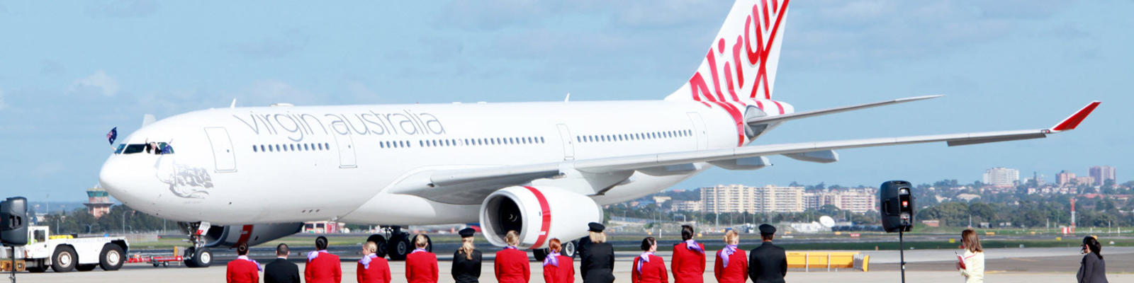 Flight crew standing on a red carpet on the runway looking at a Virgin Australia airplane