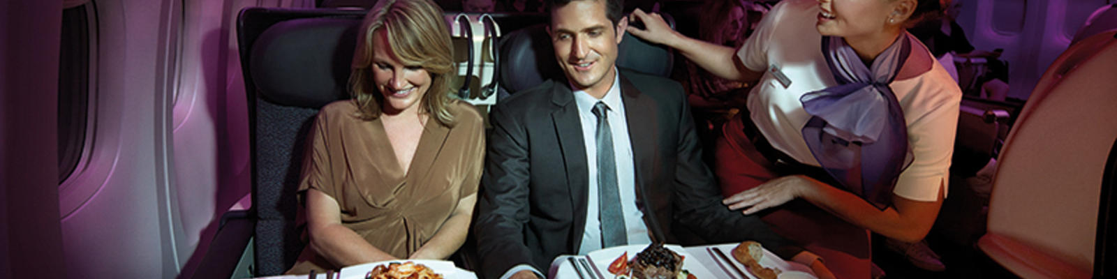 A man and a woman being served their food in Business Class on Virgin Australia