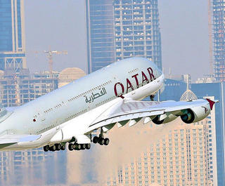 qatar a380 flying with doha skyline behind