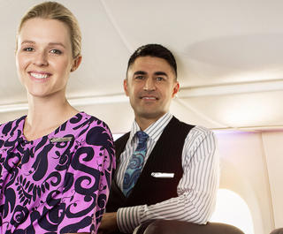 Three Air New Zealand flight attendants inside an aircraft.