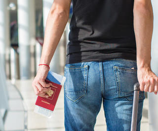 A man with a suitcase holding a passport and boarding pass.