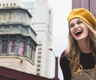 Model outdoors in Chicago laughing. She is wearing a Yellow beanie