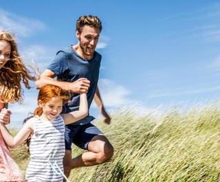 Family running along a sandune