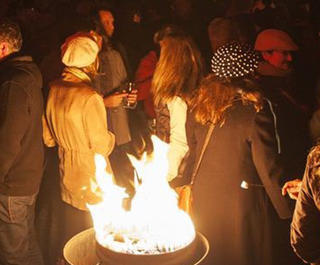 People by a fire outside at the Dark mofo festival in Hobart.