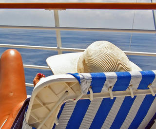 Woman sunning herself on a deck chair on a cruise ship looking at the sea.