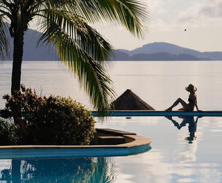 Woman sitting on the edge of the pool at a beachfront resort as the sun goes down at Hamilton Island.