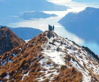 Distant view of hikers standing on a cliff against lake during winter, Queenstown