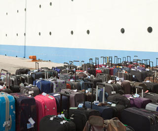 suitcases lined up on dock ready to load onto cruise ship