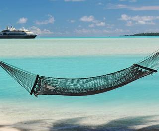 tropical island hammock with cruise ship behind