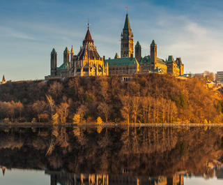 A view of Ottawa's parliament building reflecting off the surrounding water