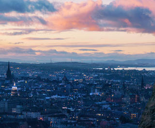 man on mountain over edinburgh sunset