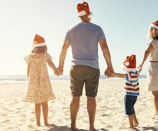 Shot of a family of four walking on the beach on Christmas. Photo: Getty Images.