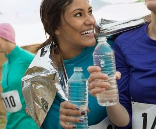 Smiling runners drinking water after marathon