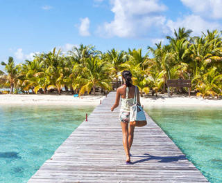 woman walking on boardwalk to tropical island