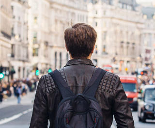 man standing in london street facing away
