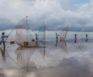 Fisherfolk cast their nets on a beach at the Mekong Delta in south Vietnam