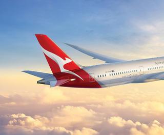 The Qantas Dreamliner flies through the clouds.