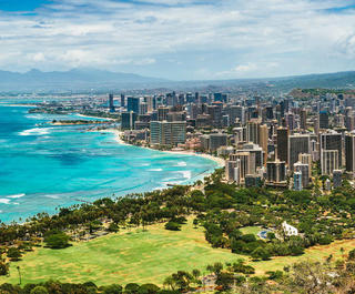Waikiki Beach stretches away with the skyscrapers of Honolulu behind, as viewed from Diamond Head, Hawaii.