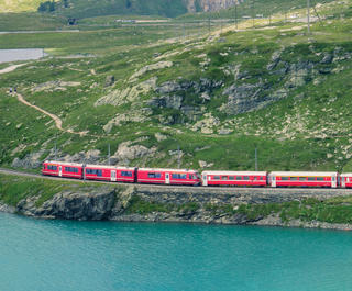 Red train going past a lake and green mountains