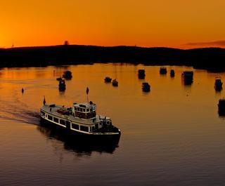 Boats at Port Stephens against an orange sky.