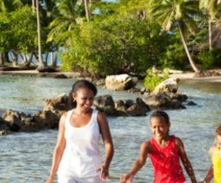 Family plays in shallow water at beach with palm tress in background