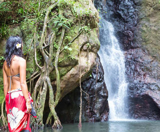 A woman stands by a waterfall in Fiji.