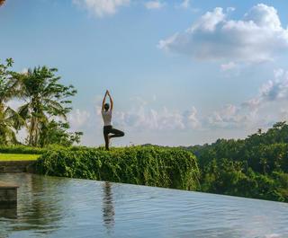 A woman performs yoga by a pool at Mandapa Ritz Carlton Ubud in Bali.