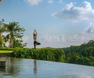 A woman performs yoga by a pool at Mandapa Ritz Carlton Ubud in Bali.