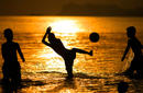 Young boys play soccer as the sunsets